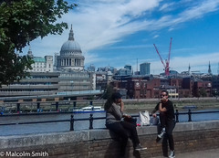 Lunch By The Thames (M C Smith) Tags: london lunch wall people man woman smoking blue sky clouds white buildings cranes river boat railings stpauls sitting riverthames bag spires green tree