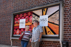 Cheese & Tomato (Silver Machine) Tags: winchester hampshire streetphotography street candid standing leaning couple ms marksspencer tomato cheese advert advertisement billboard fujifilm fujifilmxt10 fujinonxf35mmf2rwr