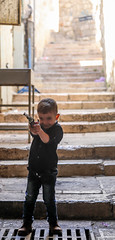 This is what happens when children are raised in regions with violent conflicts (ybiberman) Tags: israel jerusalem oldcity alquds muslimquarter boy play shooting pistol smiling candid streetphotography