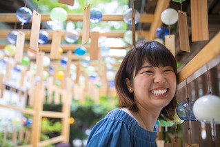 Happy young woman standing under wind chime gate