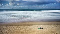 Watching surfers. Long exposure. (hajavitolak) Tags: paisaje playa landscape beach nature nubes naturaleza clouds mar sea seascape surf mirrorles sinespejo evil salinas asturias spain sony sonya7ii zeiss zeiss3528