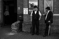 Dad's Army (Silver Machine) Tags: warontheline watercressline alresford hampshire midhantsrailway railwaystation wwii secondworldwar festival 40s 1940s men standing talking cigar bowlerhat umbrella sandbags blackwhite bw mono monochrome fujifilm fujifilmxt10 fujinonxf35mmf2rwr
