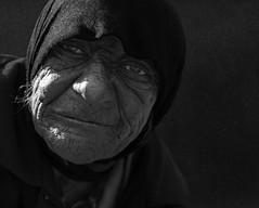 Old Age (Ales Dusa) Tags: woman portrait outdoor face oldage oldwrinkledwoman wrinkles closeupportrait streetportrait alesdusa bw blackandwhite streetshot elderly dramaticportrait strongcontrast homeless beggar storytelling candid canon5d blackbackground scarf noirportrait