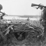 Vietnam War 1968 - SOC TRANG - Vietnamese Mother and Child Peer out of Hole thumbnail
