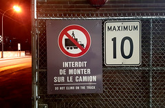 Do not climb on the truck (dammit) (Coastal Elite) Tags: interdit de monter sur le camion do climb truck mill montreal griffintown industrial farine five roses minoterie adm factory industriel sign affiche signe warning avertissement interdiction prohibition prohibited prohibit trucks van vans workers camions parking fence hazard stick figure figures peril dont red circle night montréal nightshot clôture road maximum trespass trespassing climbing grimper