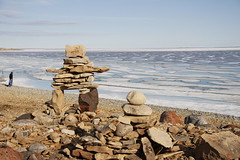 Inukshuk or Inuksuk on a rocky beach with ice on the ocean in late June in the high arctic (Blue Tale) Tags: water seashore beach sea rock ocean stone boulder nature travel landscape outdoors summer balance shore ancient arctic cambridge bay kitkimeot canada coastal cold community culture designe westernarctic inuit inukshuk inuksuk isolated journey land landmark marker native north northern nunavut polar region rocks structure symbol tourism tradition ice farnorthe higharctic inuksuit