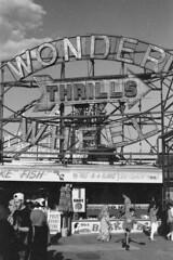 Cheap Thrills (Magnus Bergström) Tags: 123bw city york new newyorkcity nyc united states america usa unitedstates streetphotography street monochrome canon ae1 kodak bw400cn expired 135 film 35mm analog bw kodakbw400cn blackandwhite blackwhite black white brooklyn coney island amusement park wonder wheel people boy man ball hat ride