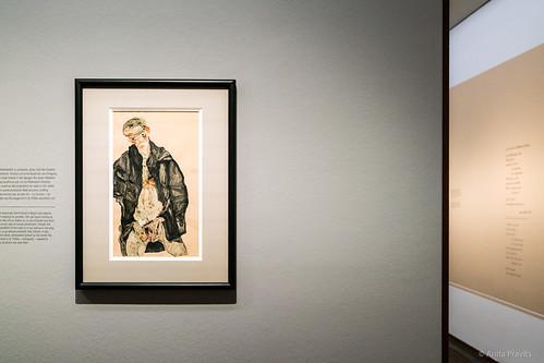 Egon Schiele: Selbstbildnis als Halbakt in schwazer Jacke / Seminude Self-Portrait in Black Coat, 1911