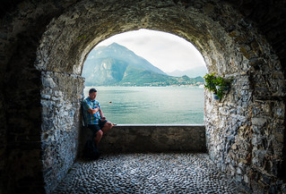 Guy Chilling at Lake Como with mountain view.