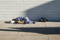 crashed (rappensuncle) Tags: crashed sleep onthestreet blanket homeless person sleeping sunlight shadow wall oneperson objects street