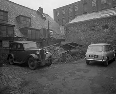 Negative No: 1963-1031 - Negatives Book Entry: 00-05-1963_TP/Valuation_17-7 (Mancunican Way) Area_Chancery Lane to Tipping Street (archivesplus) Tags: manchester england 1960s townhallphotographerscollection morris 8 austin seven mini mk1 oldcar oldwall bricks oildrum
