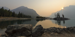 Lake Minnewanka (fred.colbourne) Tags: mountain banffnationalpark alberta lakeminnewanka sunrise smoke lake water wideangle sun flare trees rocks canada sunburst reflections
