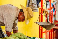 Banana Vendor & Scale, Piedecuesta Colombia (AdamCohn) Tags: adamcohn colombia kmtoin piedecuesta santanderdepartment bananas cowboyhat geo:lat=6983969 geo:lon=73051430 geotagged market marketplace street streetmarket streetphotography vendor wwwadamcohncom yellow santander man hat