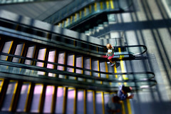 riding across the grid (KevinIrvineChi) Tags: escalators cleveland museum art grid girl sunlight indoors courtyard tiltshift aperture priority sony dscrx100 steps shadows lobby handrails yellow shiny