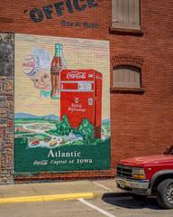 Capitalization (Pete Zarria) Tags: iowa coke coca cola bottle soda pop ghost sign cans atlanta red brick small town