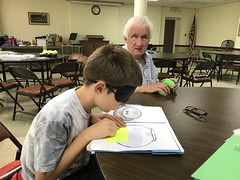 "Photo 2: Participant wearing learning shades doing a folder game with a mentor • <a style=""font-size:0.8em;"" href=""http://www.flickr.com/photos/29389111@N07/37035115646/"" target=""_blank"">View on Flickr</a>"