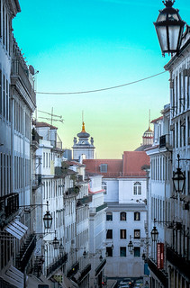 is this Minas Tirith from Lord of the Rings? NO, looking down the steep Rua Nova Do Almada with the tops of  the Camara Municipal de Lisboa and the Arco da Rua Augusta visible above red tiled roofs, Lisbon, Portugal