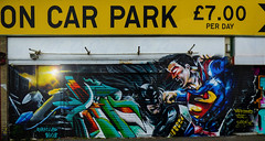 On Car Park £7.00 Per Day (Steve Taylor (Photography)) Tags: darkisseddayze margate batman superman 5 highstreet fighting punching batmanvssuperman art graffiti mural streetart carpark sign colourful uk gb england greatbritain unitedkingdom glow