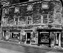 Shops at Kirkby Lonsdale (Snapshooter46) Tags: shops kirkbylonsdale stonebuildings cumbria newroad incline monochrome blackandwhite photosketch