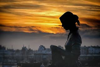 Fisherwoman statue against the setting sun.