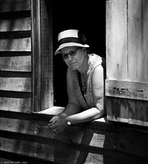 Shotgun Shack. (Neil. Moralee) Tags: neilmoralee usa2017neilmoralee woman lady girl portrait framed window shack wooden hat glasses sunnies sunglasses hot sunlight dappled shadows shotgun house new orleans louissianna face black white bw bandw blackandwhite mono monochrome poor poverty small shutter nikon d7200 neil moralee pretty mature sad usa farm plantation cotton cottage dwelling