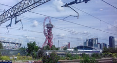 Passing The Olympic Park (M C Smith) Tags: stratford olympicpark train powerlines overhead buildings sky blue clouds white fence railings track lamps red housing flats green yellow grass weeds