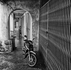 Down A Side Street (kieronjameslong) Tags: leicaq leica monochrome bike motorbike street sidestreet alley arcade arch archway woman streetphotography architecture building wideangle perspective kuching sarawak malaysia borneo asia fareast southeastasia blackandwhite