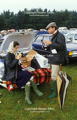 SLOANE RANGERS PICNIC BUCKS FIZZ WINDSOR GREAT PARK CAR POLO MATCH (Homer Sykes) Tags: sloaneranger bucksfizz drinking champagne tweed posh wealthy rich 1980s 80s flatcap hat picnic polo windsorgreatpark carpark berkshire hermes headscarf blue barbour waxedjacket coat tartan blanket rug hunter green boots wellies wellingtons sportscar upperclass country clothing clothes fashion fashionable archivestock britain england uk british society english windsor gbr