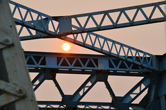 The sun sets on the blue bridge (James_D_Images) Tags: sun smoke forest fire haze orange cast filtered steel bridge beam crossbrace rivets blue rust obsolete lines pattern angles