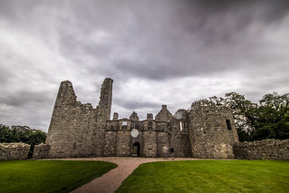 Tolquhon castle stands still under looming clouds while visitors blur in first drops of rain, colour, long exposure, Aberdeenshire, Scotland