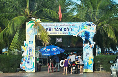 Arriving at the beach (Roving I) Tags: families checkingin arriving gateways entrances signs beaches palmtrees motorcycles flags umbrellas advertising revive drinks security guards plasticchairs leisure lifestyle recreation danang vietnam