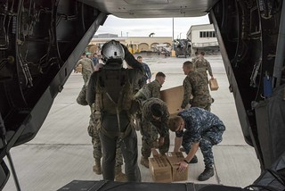 Sailors and Marines unload military field rations from an MV-22 Osprey aircraft in San Juan,