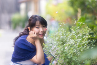 Portrait of young woman sitting beside green leaves