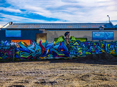 Saga (Steve Taylor (Photography)) Tags: saga lying wings dtr dtrcrew art graffiti mural streetart colourful cool man newzealand nz southisland christchurch canterbury gravel shadow sunny sunshine sky cloud