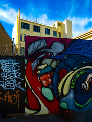 RESK it for a Beskuit (Steve Taylor (Photography)) Tags: resk jacob yikes fromthegroundup bluesky art graffiti mural tag streetart building fence colourful vivid newzealand nz southisland canterbury christchurch cbd city autumn sky sunny sunshine cloud barbedwire