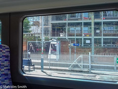 A Passing Glimpse Of Ilford (M C Smith) Tags: train window platform station ilford building construction fence railings bench scaffolding trees green seats advertising board shadows lamps