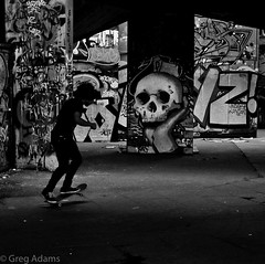 Dark Passage (Greg Adams Photography) Tags: london skateboard man bw blackandwhite skull graffiti england uk greatbritain silhouette travel under underneath cement concrete paint spraypaint britain movement passing hhsc2000 colorblind street streetphotography