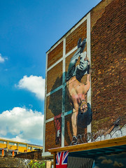 At Ease (Steve Taylor (Photography)) Tags: barechested busby guard soldier handstand acrobatics art graffiti mural tag streetart brick wall fun uk gb england greatbritain unitedkingdom london shadow jacket flag unionjack