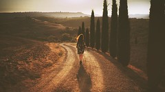 Into Tuscany (der_peste) Tags: woman women walking exploring sunlight day mood tuscany tuscan toskana italy italia cypresses cypress road way path shadow light morning atmosphere zeiss 35mm f14