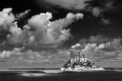 A Masterpiece of Gothic Architecture (Christian Hacker) Tags: montsaintmichel normandy france blackandwhite mono monochrome bw canon50d holiday vacation touristy tourism clouds dramatic summer september gothic architecture island abbey unesco worldheritagesite beach coastal cathedral mount masterpiece tamron impressive illuminated handheld manche fortified fortification monastery landmark tidal historic history attraction digital photoshop
