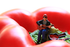 There ain't no cure for the capsicum blues (alideniese) Tags: macro closeup littleperson guitarist busker 7dwf alideniese capsicum bellpepper redpepper bokeh guitarplayer smallperson figure vegetable highkey whitebackground light colour red whimsical playful fun