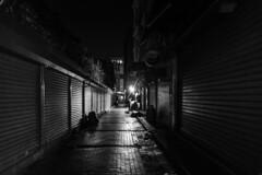 loneliness knows no working hours / the light at the end of the street (Özgür Gürgey) Tags: 2017 20mm bw d750 darkcity eminönü nikon voigtländer evening grainy lines loneliness lowlight shadow street istanbul