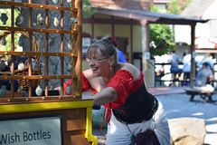 A Woman With Some Wishes (MTSOfan) Tags: parf pennsylvaniarenaissancefaire vendor woman sales push cart wishbottles wishing wish smile