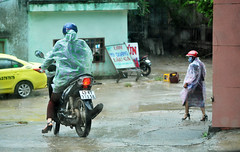 Ride or walk (Roving I) Tags: weather wet women rain raincoats heels helmets signs street taxis vietnam villages danang motorcycles