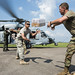 Sailors and Soldiers load water onto an MH-60S Sea Hawk helicopter.