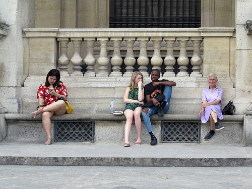 Personnes assises devant l'entrée du Louvre