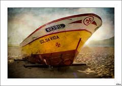 SOL DA VIDA (V- strom) Tags: barca barque portugal nazaré mar océano ocean arena sand amarillo yelow rojo red sol sun ocaso sunset cielo sky viaje travel luz light recuerdo memories texturas textures abandonado abandoned stilllife detalles