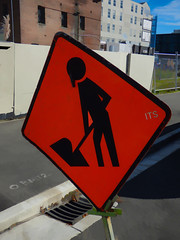 ITS a Hooter (Steve Taylor (Photography)) Tags: hooter working sign its drain road construction street building fence chainlink blue brown orange green cream contrast grey metal tarmac newzealand nz southisland canterbury christchurch cbd city grass menatwork