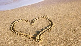 The drawing heart on sand. Heart is washed away by a sea wave.