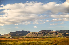 Icelandic Counrtyside (wyojones) Tags: iceland snæfellsnespennisula clouds mountains farms barns houses bales baleage haylage balesofhay plastic marshmellows cliffs grass green